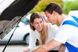Frau spricht mit Automechaniker in Werkstatt