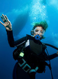 Woman scuba diver under boat