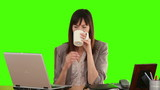 Businesswoman drinking a cup of tea at her desk