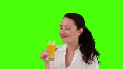 Dark-haired woman drinking orange juice