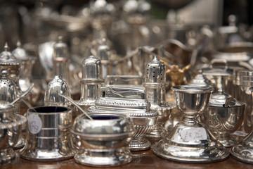 Silver ornamental objects on market table