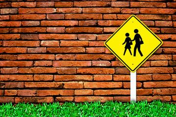 school warning sign on brick wall