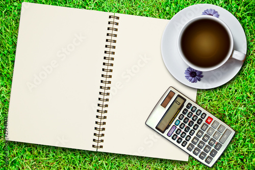 white cup of coffee and calculator