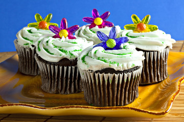 Cupcakes with sprinkles and plastic flowers