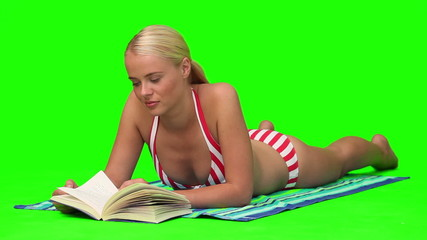 Pretty blond woman lying  while she is reading a book