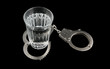 Alcoholism concept, glass with vodka and handcuffs