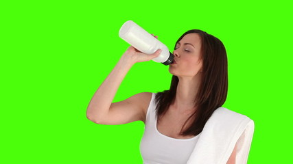 Brunette woman after sport drinking water