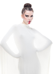 a conceptual studio portrait of a young woman dressed in white.