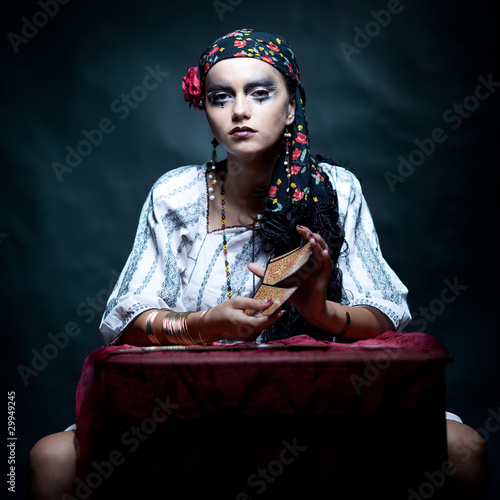 a portrait of a gypsy fortune teller mixing the tarot cards.
