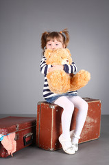 beautiful girl sits on an old suitcase with a toy in hands.