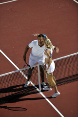 happy young couple play tennis game outdoor