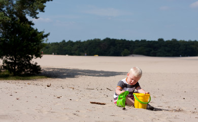 little boy is playing in the sand in the nature