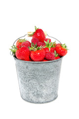 strawberries and raspberries in a bucket isolate over white