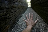 Hand Reaching Down Narrow Alley Towards Light