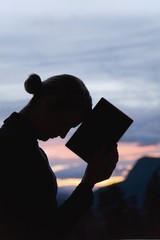 Silhouette Of Woman With A Book