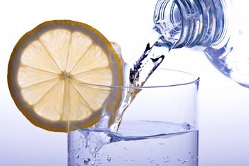 Wasserglas mit Zitrone eingiessen