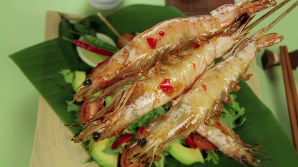 Three shrimps being pushed into a shot over a salad.