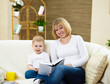 little boy and his mother at home reading a book