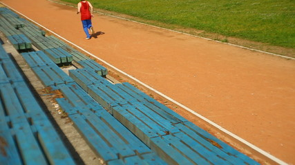 young man running through the stadium track
