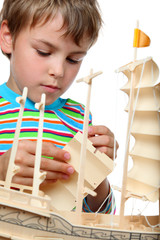 Small boy in striped shirt works with zeal on artificial ship, h