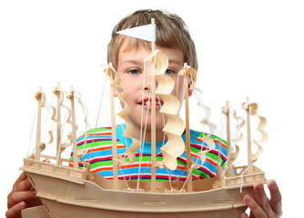 Small boy in striped shirt holds artificial wooden ship