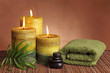 Spa products with green candles, stones and towel
