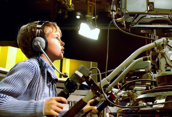 Little boy with headphones and microphone looks to camera