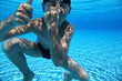 Boy dives under water in  pool and closes  nose  hand