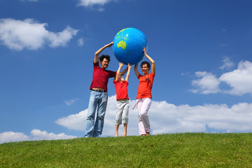 Boy with  mother and father stand on  grass and lift an globe
