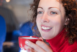 Young woman drinks coffee from the red cup on the airplane