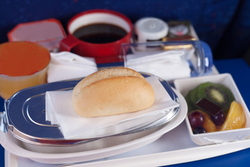 Tray of food on the plane. Focus on a bun.