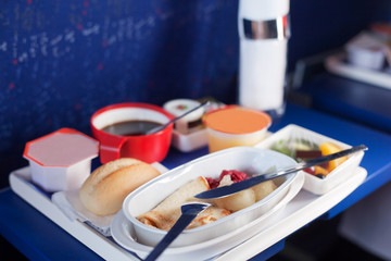 Tray of food on the plane. Focus on a plastic cruet