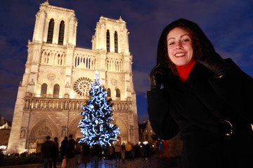 smiling woman stands on square in front of  Notre Dame