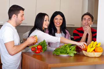 Happy friends in kitchen with vegetables