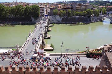 Tourists going on Sant' Angelo Bridge at summer day in Rome