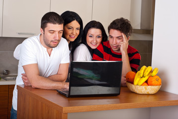 Group of friends using laptop in kitchen