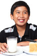 Portrait of a happy young boy holding a glass of milk.