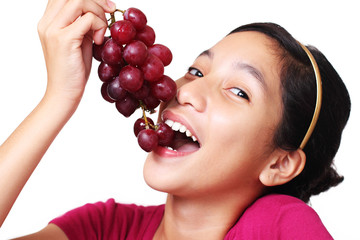 Young asian teenager eating a bunch of grapes.