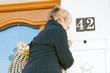 Frau schaut in den Briefkasten