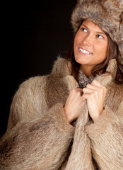 young woman in a fur coat and hat, black background.