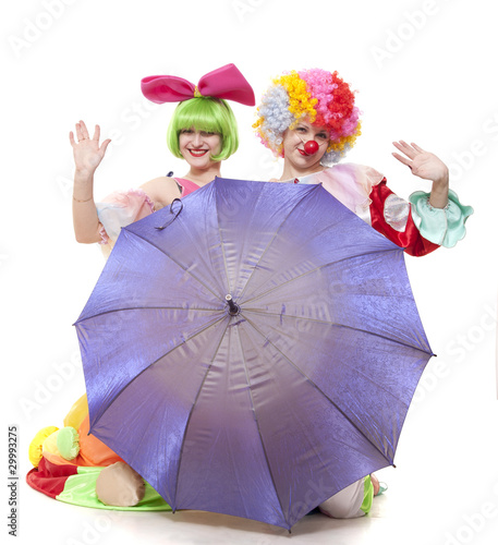 Clowns behind an umbrella wave hands at parting