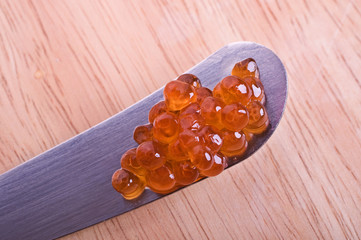 Red caviar on a tip of a knife