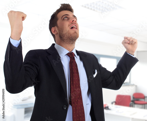 Happy businessman gesturing success in the office