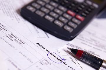 calculadora, facturas y bolígrafo