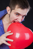 Young guy holding a red heart-shaped balloon