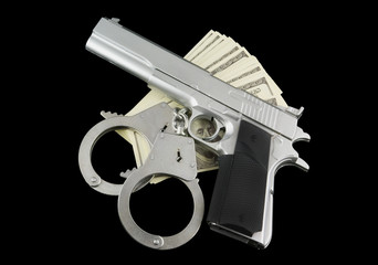 Stack of money, gun and handcuffs isolated on black