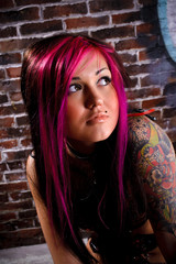 Attractive tattooed girl studio portrait, brick wall at backgrou