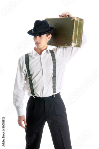 young gangster man holding an old suitcase