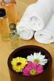 Wooden bowl with flowers and spa items in background poster