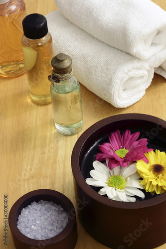 poster of Wooden bowl with flowers and spa items in background
